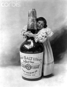 ca. 1897 --- Little Girl Hugging Bottle --- Image by © CORBIS