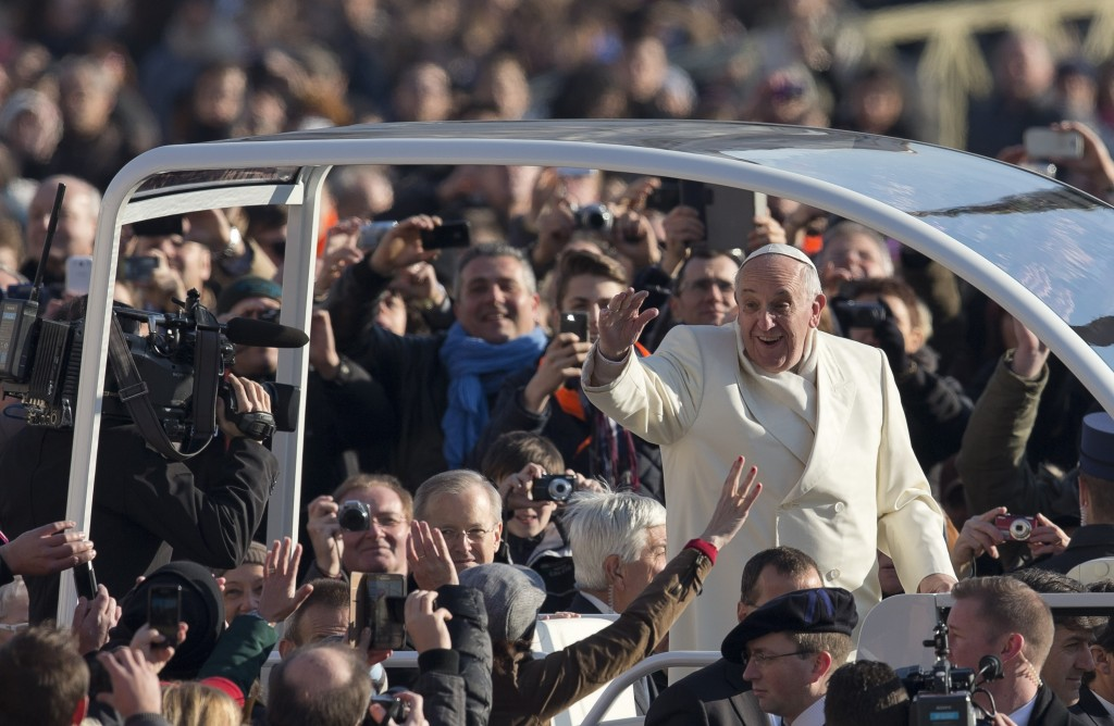 Pope Francis arrives in a rooftop-covered-pope-mobile for his weekly general audience in St. Peter's Square at the Vatican, Wednesday, Dec. 11, 2013. (AP Photo/Alessandra Tarantino)