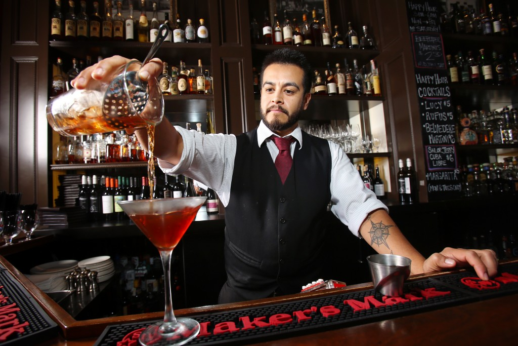 Bartender Neil Espinosa pours a Manhattan as one of Stark's Steakhouse's winter cocktails in Santa Rosa on Wednesday, October 2, 2013. (Conner Jay/The Press Democrat)